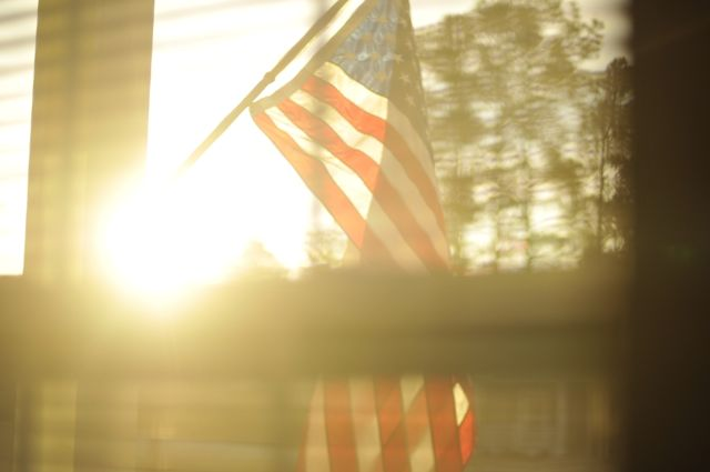 My flag as the sun peeks over the house across the street letting me know that the morning is awake.