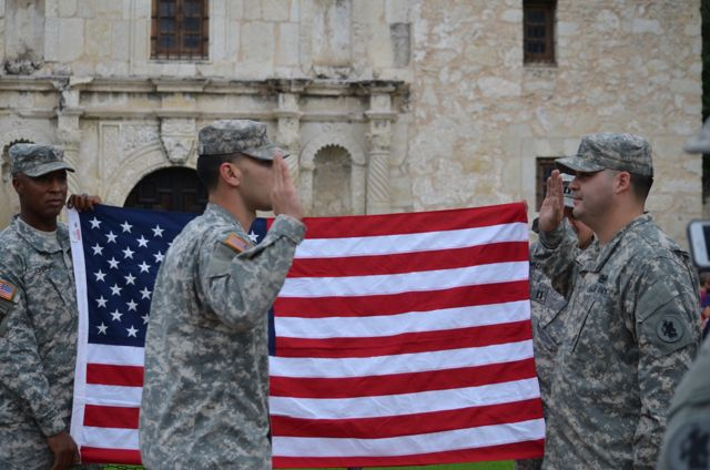 A group of soldiers showed up to take pictures of the flag in front of the Alamo.